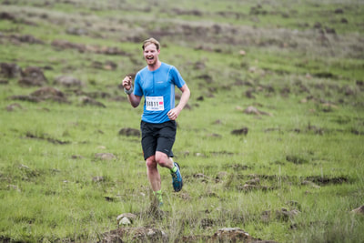 Russel Canning all smiles and fist pimps as he recognises the camera, clearly loving his trail run - (c) Andrew Mc Fadden / BOOGS Photography