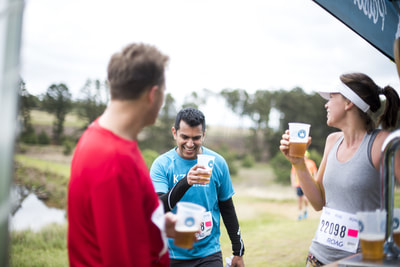 Santosh Bugwandin sharing a joke over a beer with some fellow trail runners - (c) Andrew Mc Fadden / BOOGS Photography